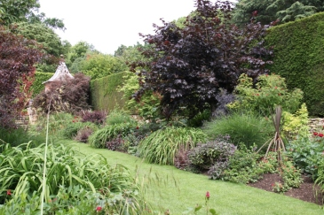 Mixed borders have shrubs, hardy perennials and tender plants in red and bronze