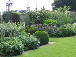 Tasteful colour schemes and a light trellis backdrop make this border a real success